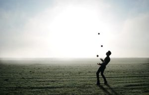 A man standing on a flat field and juggling apples.